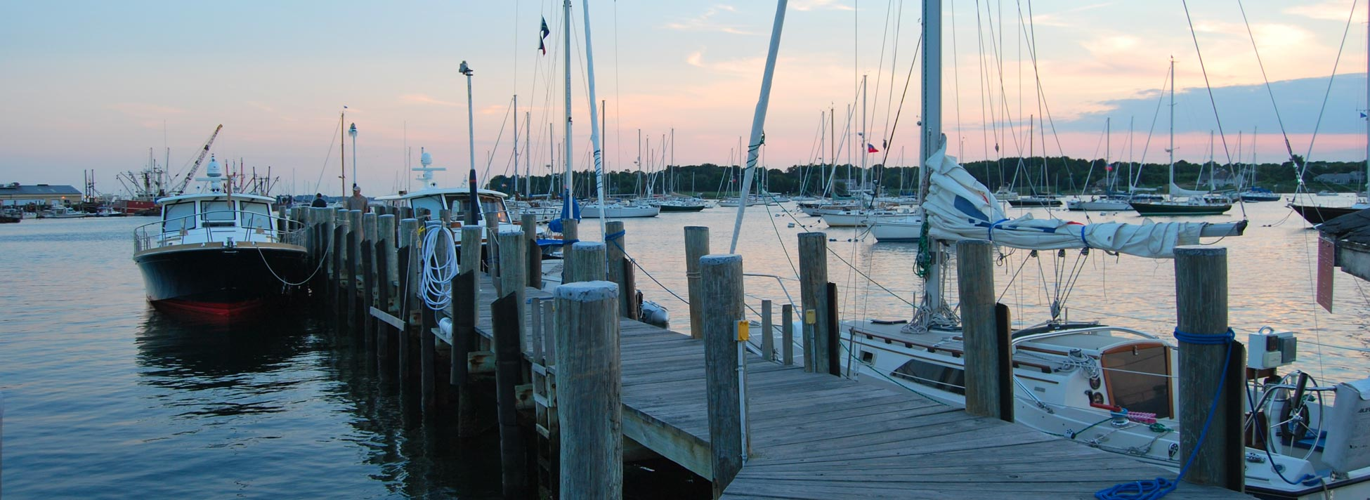 Photo of sailboats at dock with sunset sky in background